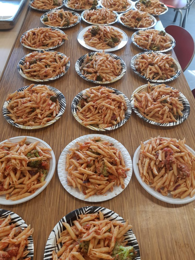 Veertien borden met pasta op een tafel